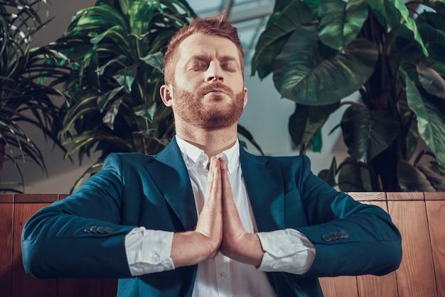 Trabajador en traje meditando en el banco en la oficina. Foto Premium