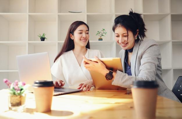 Trabajadora sostenga la tableta y hablando de negocios con su pareja, tome café mientras trabaja desde casa Foto Premium