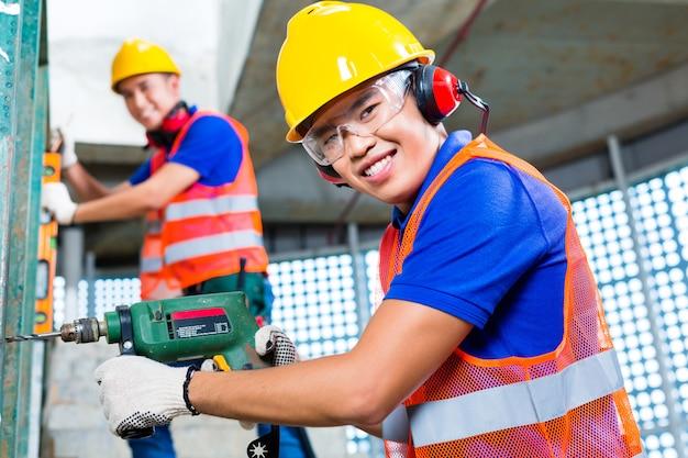 Trabajadores asiáticos de la construcción que perforan en las paredes del edificio Foto Premium