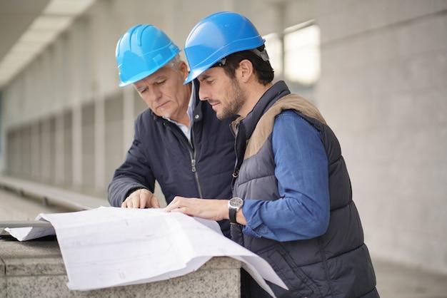Trabajadores en cascos que consultan sobre planos en vista de edificio moderno Foto Premium