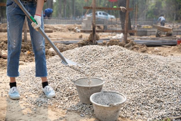 Trabajadores de la construcción llevando una pala al sitio de construcción Foto gratis