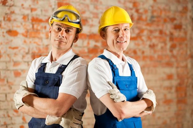 Trabajadores de la construcción de pie con los brazos cruzados Foto Premium