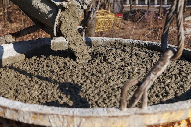 Trabajadores de la construcción que vierten el concreto mojado usando el cubo concreto Foto Premium