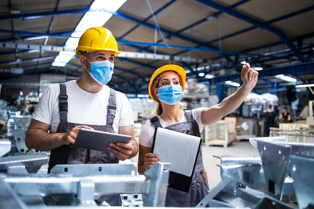 Trabajadores de fábrica con mascarillas protegidas contra el virus corona haciendo control de calidad de producción en fábrica Foto gratis