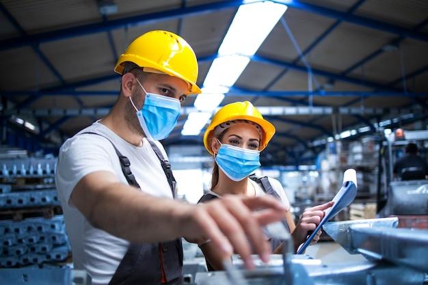 Trabajadores industriales con mascarillas protegidas contra el virus corona discutiendo sobre piezas metálicas en la fábrica Foto gratis