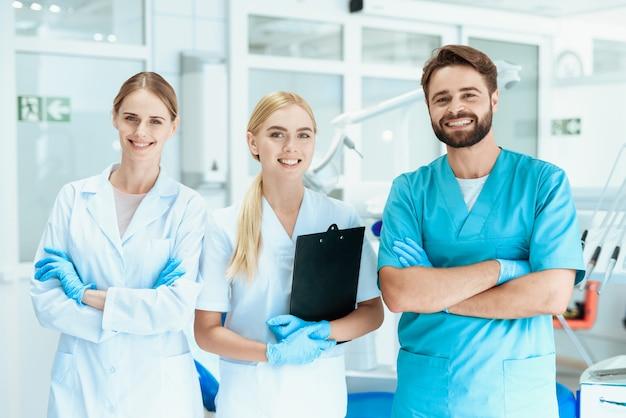 Trabajadores médicos con equipo de dentista de pie y sonriente. Foto Premium