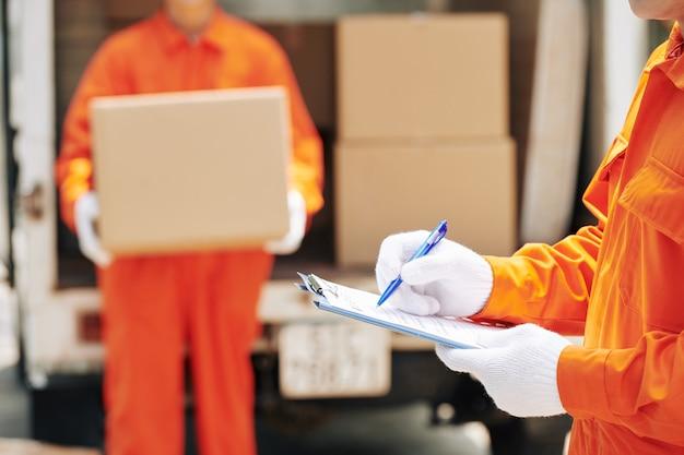 Trabajadores de mudanzas domésticas marcando casillas Foto Premium