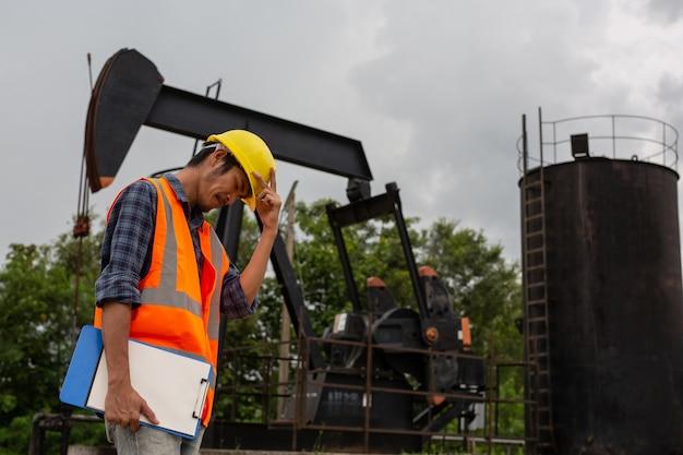 Trabajadores de pie y comprobando al lado de bombas de aceite. Foto gratis