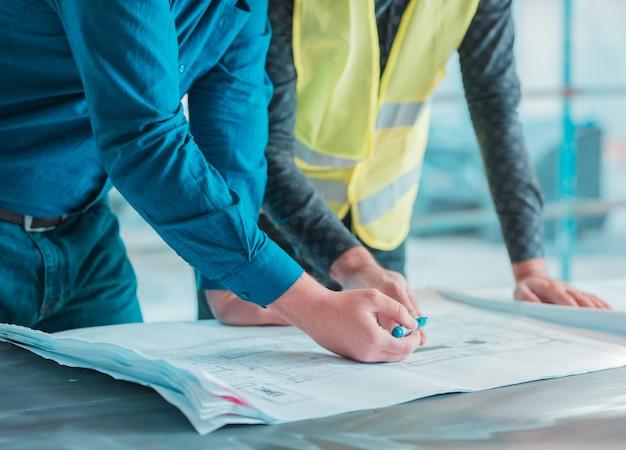 Trabajadores que abandonan el plan arquitectónico de un proyecto. Foto gratis