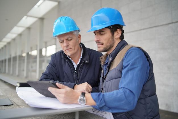 Trabajadores que consultan sobre plano con la tableta en vista del edificio moderno Foto Premium