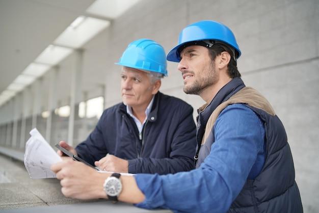 Trabajadores que consultan sobre plano en vista de edificio moderno Foto Premium