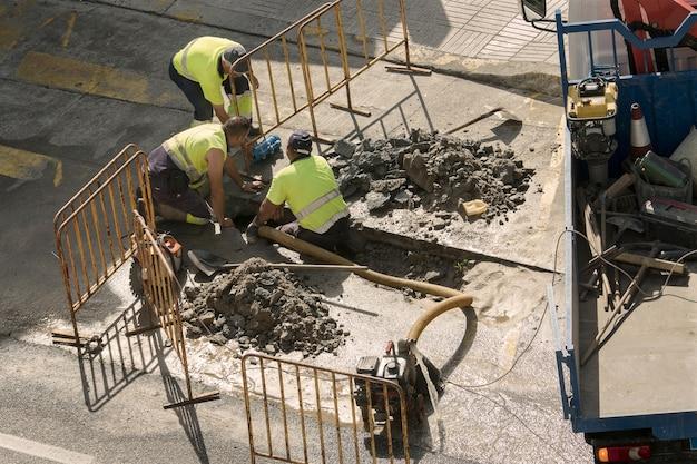 Trabajadores reparando una tubería de agua rota en la carretera Foto Premium