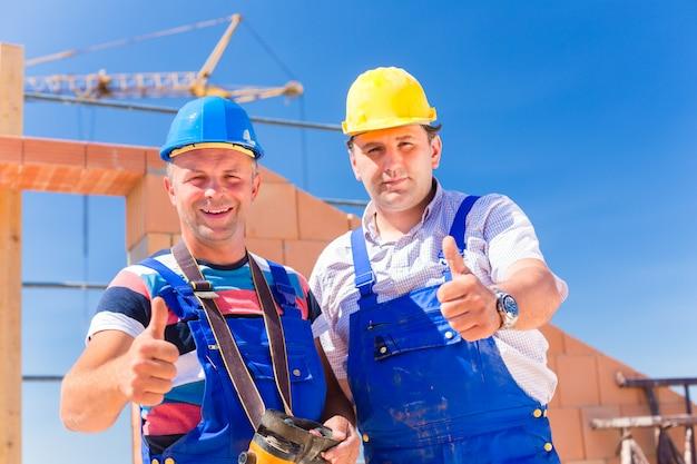 Trabajadores del sitio de construcción construyendo paredes en la casa Foto Premium