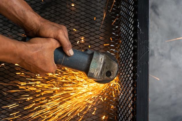 Los trabajadores varones cortan y sueldan metal con chispa. Foto gratis