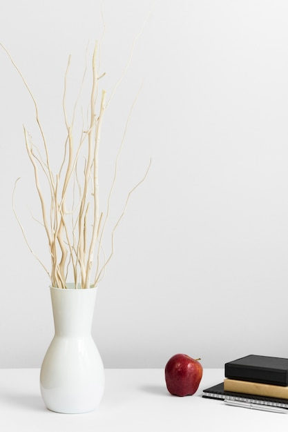 Trabajo contemporáneo con jarrón y manzana en escritorio Foto gratis