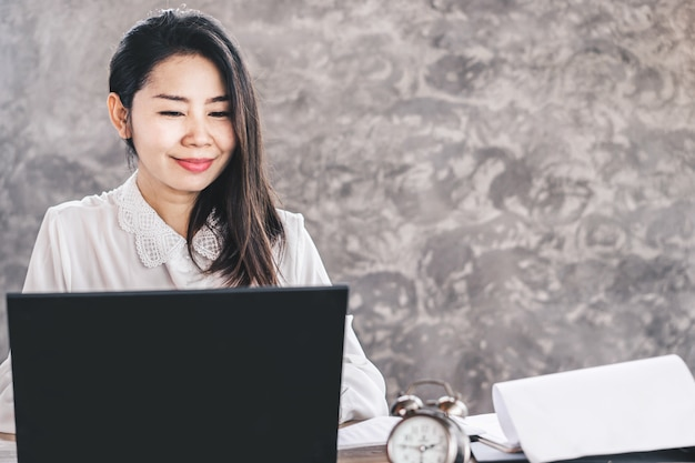 Trabajo feliz asiático de la mujer de negocios en el ordenador Foto Premium