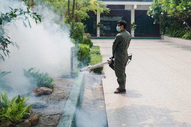 El trabajo del hombre se empaña para eliminar el mosquito y prevenir la propagación de la fiebre del dengue y el virus zika Foto Premium