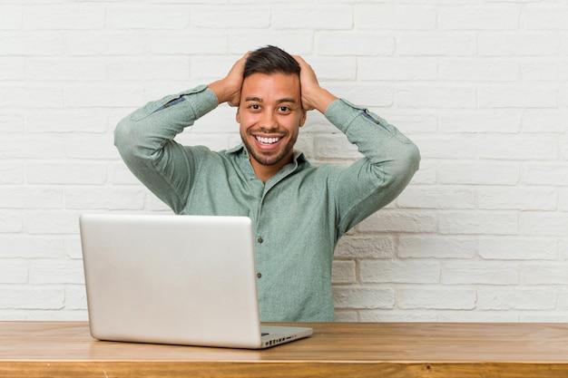 El trabajo que se sienta del hombre filipino joven con su computadora portátil ríe con alegría mantener las manos en la cabeza. Foto Premium