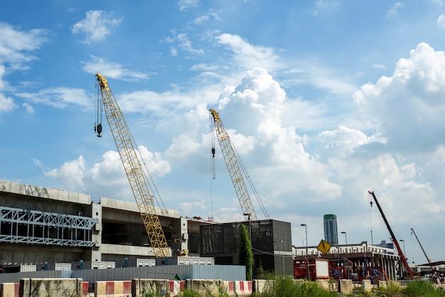 Trabajos de construcción de grúas y edificios y cielo azul. Foto Premium