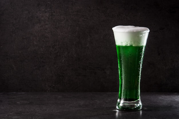 Tradicional cerveza verde del día de san patricio sobre fondo negro copia espacio Foto Premium