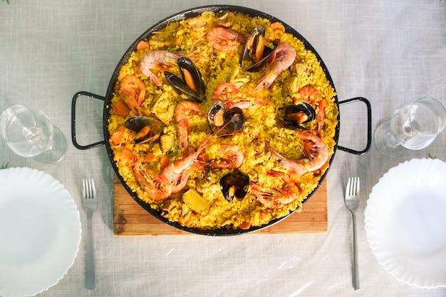 Tradicional plato de paella española con langostinos y mejillones. Foto Premium