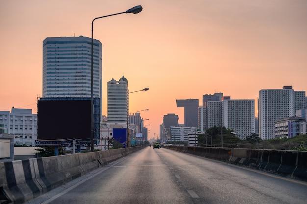 Tráfico de carretera con edificio en la ciudad al atardecer Foto Premium