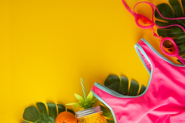 Traje de baño rosa y tarro de piña para jugo. fondo de verano con espacio de copia. Foto Premium