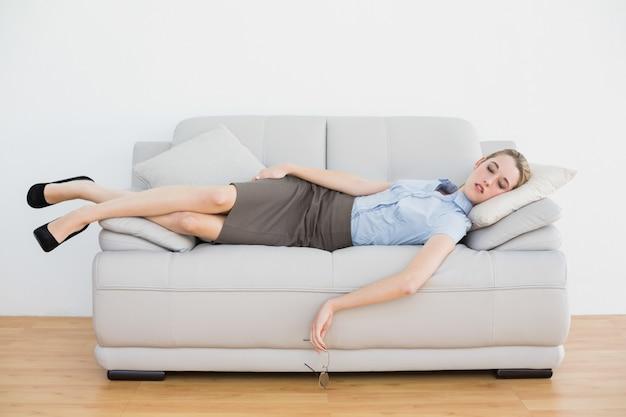 Tranquila empresaria elegante durmiendo mientras está acostado en su sofá Foto Premium