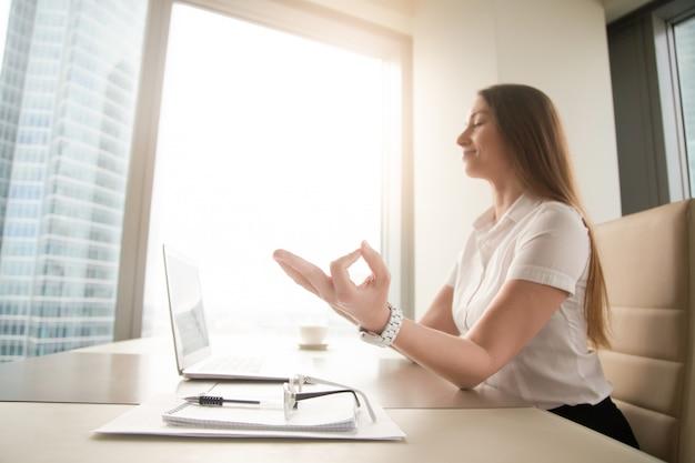 Tranquila empresaria pacífica practicando yoga en el trabajo, meditando en la oficina Foto gratis