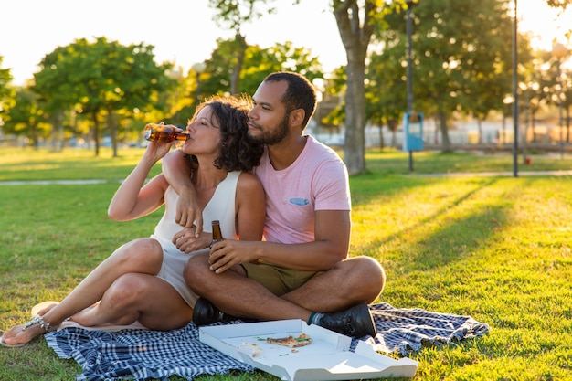 Tranquila pareja dulce disfrutando de una cena en el parque Foto gratis
