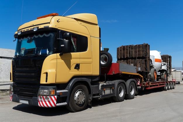 Transportes pesados de gran tamaño en camión. alta carga industrial enviada en la red de arrastre. Foto Premium