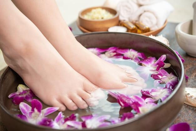 Tratamiento de spa y producto para pies femeninos y spa de manos. flores de orquídeas en cuenco de cerámica. Foto gratis