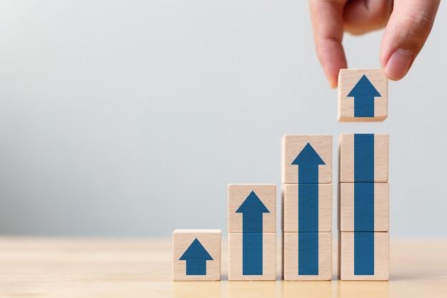 Trayectoria profesional de escalera para el concepto de proceso de éxito de crecimiento empresarial. mano arreglando el apilamiento de bloques de madera como escalón con flecha hacia arriba Foto Premium