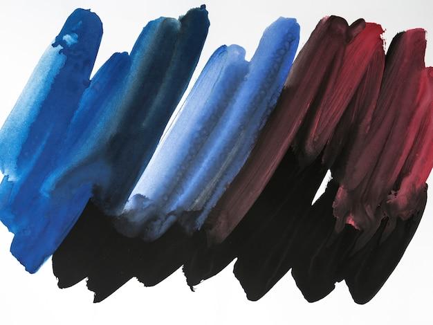 Trazos de pincel azul y rojo sobre fondo blanco Foto gratis