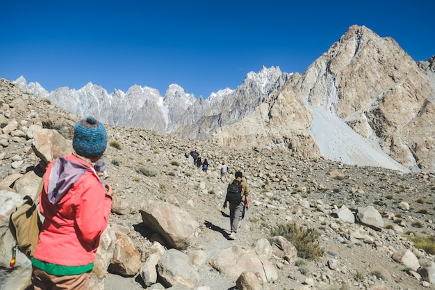 Trekkers caminando por la pista en passu, gilgit baltistan, pakistán. Foto Premium