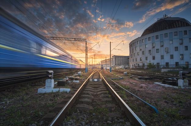 Tren de pasajeros de alta velocidad en movimiento en la vía del tren al atardecer Foto Premium
