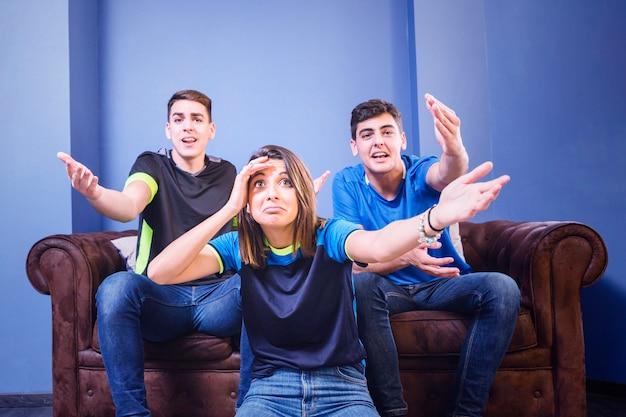 Tres aficionados en sofá no se lo pueden creer Foto gratis