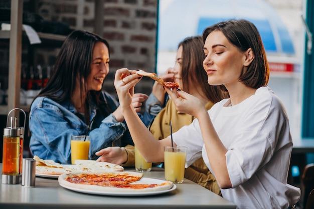 Tres amigas comiendo pizza en un bar Foto gratis