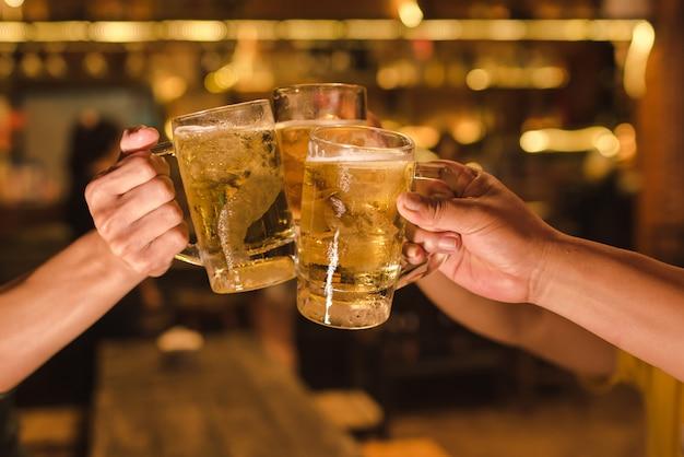 Tres amigos brindando con vasos de cerveza ligera en el pub Foto Premium