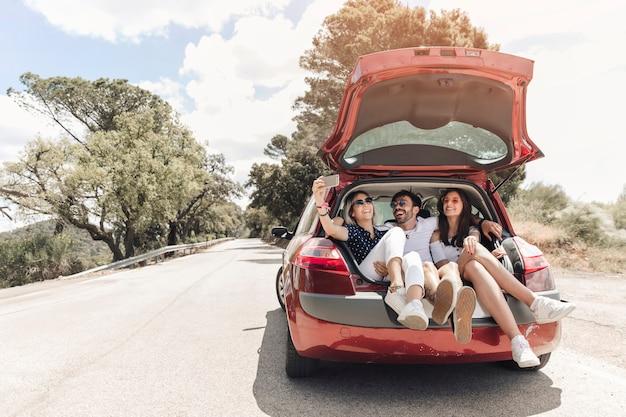 Tres amigos sentados juntos en el baúl del auto tomando autorretrato en la carretera Foto gratis