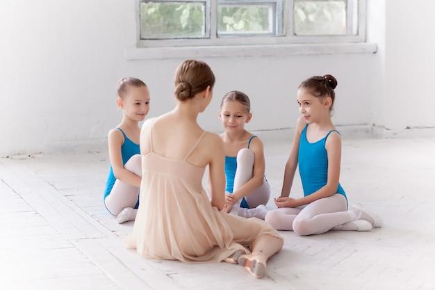 Tres bailarinas bailando con profesora de ballet personal en estudio de danza Foto gratis