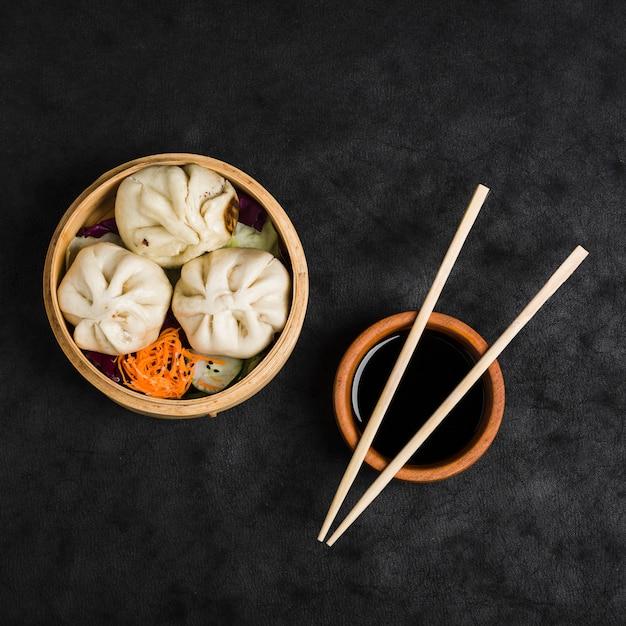 Tres bolas de masa hervida con ensalada en vaporeras y tazón de salsa de soja con palillos sobre fondo de textura negra Foto gratis