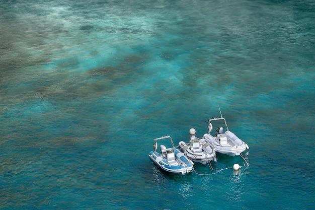 Tres botes de motor inflables se colocan en la bahía cerca de la costa en un cálido día de verano. Foto Premium
