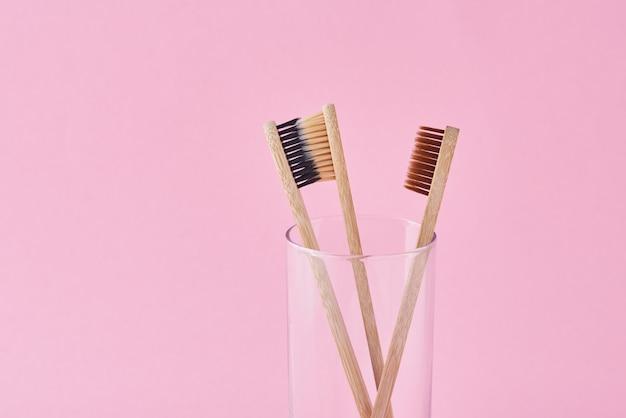 Tres cepillos de dientes de bambú de madera en vidrio sobre un fondo rosa. concepto de higiene del cuidado dental Foto Premium