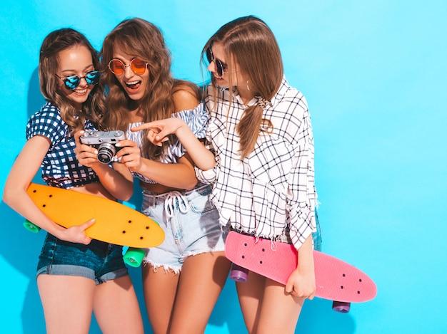 Tres chicas guapas con estilo hermosas sonrientes con patinetas coloridas centavo mujeres en ropa de camisa a cuadros de verano posando. modelos tomando fotos con la cámara de fotos retro Foto gratis