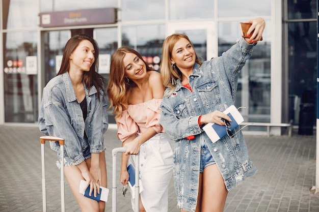 Tres chicas guapas de pie junto al aeropuerto Foto gratis