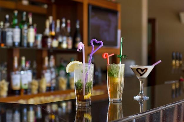 Tres cócteles en el bar - mojito con hielo y paja, pina colada con corazón de chocolate Foto Premium