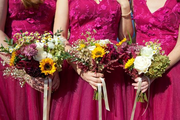 Tres damas de honor con vestidos de encaje lila con ramos de flores frescas, enfoque selectivo Foto Premium