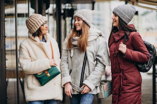 Tres estudiantes en traje de invierno en la calle Foto gratis