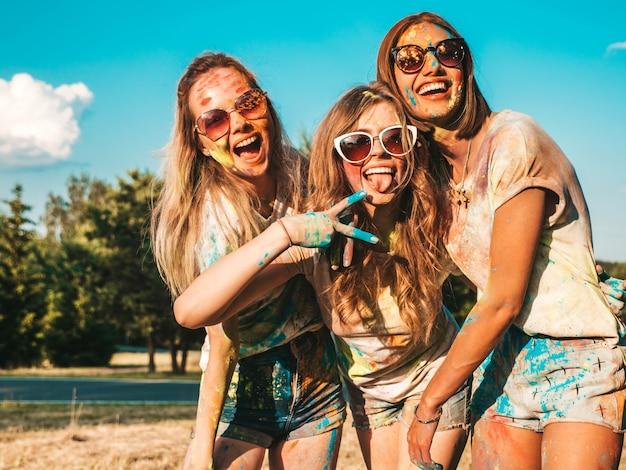 Tres hermosas chicas sonrientes posando en la fiesta de holi Foto gratis